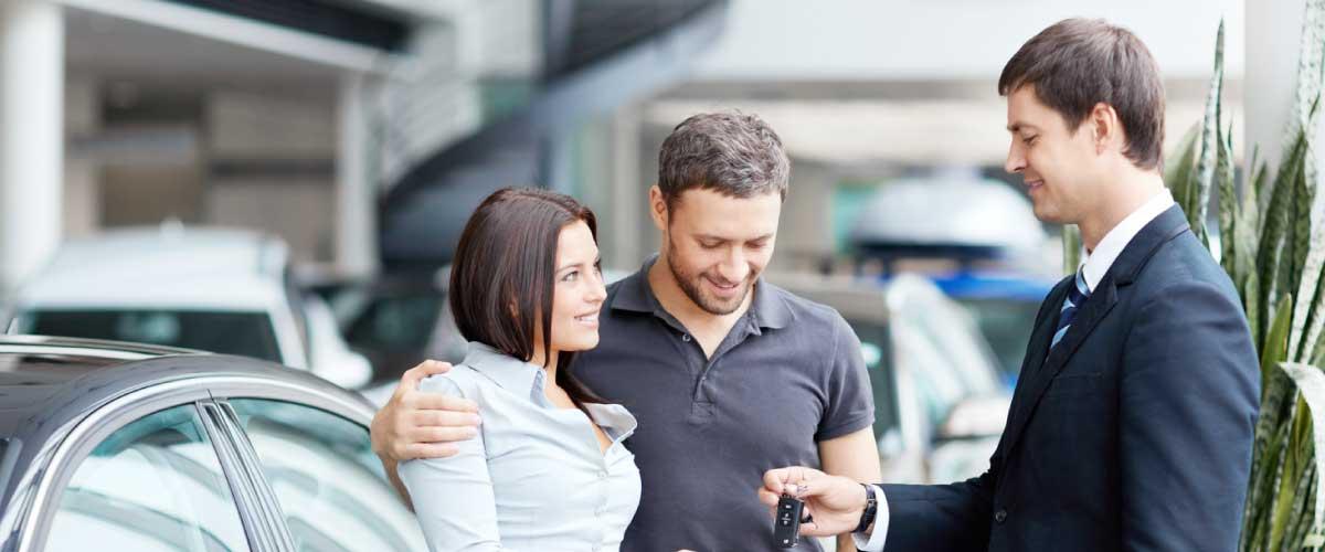 hombre y mujer con llave del auto saliendo de una aseguradora