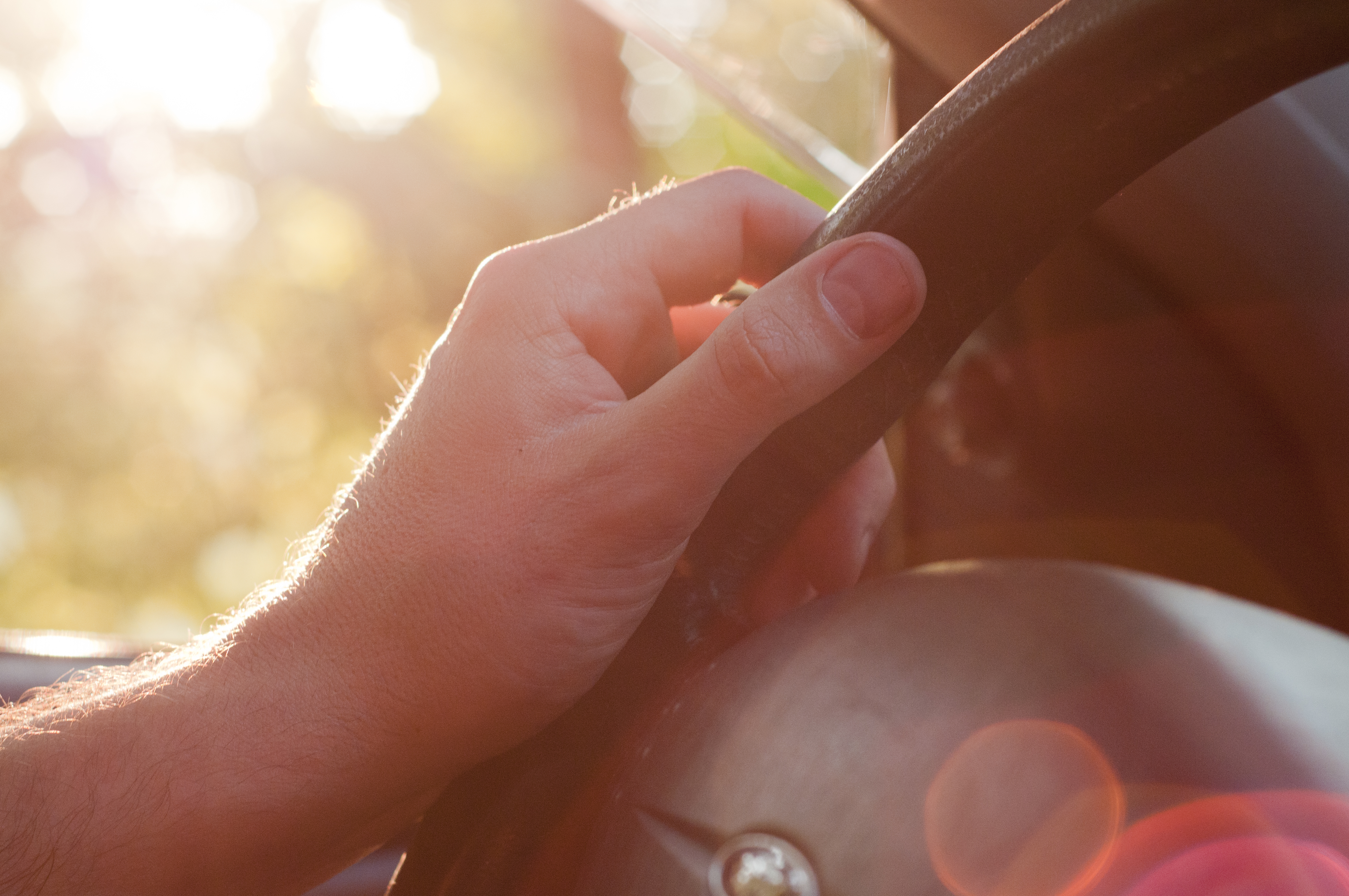 Man driving his car. Driving - young man's hand holding the steering wheel